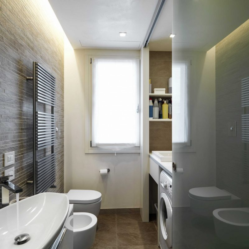 interior view of a modern bathroom in foregorund the washbasin and the tap to right the washing machine